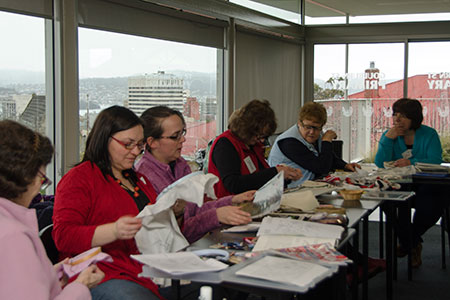 Guild members sitting at a table stitching and chatting during a stitching day